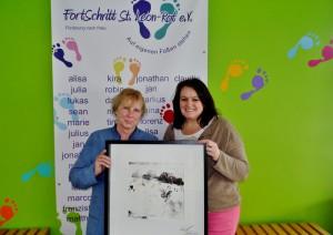 Vorsitzende Susanne Huber re. bei einer Spenden-Übergabe (ersteigertes signiertes Bild)